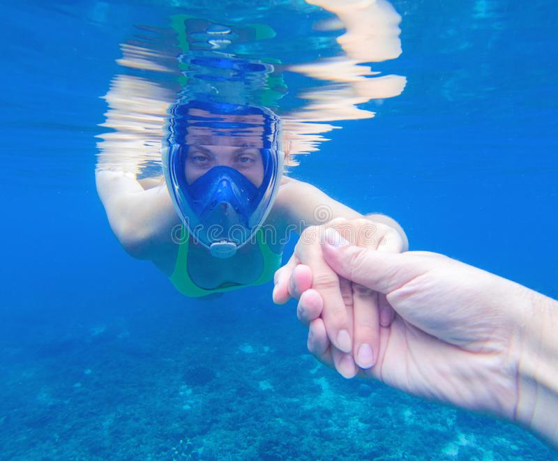 Snorkeling woman in full-face snorkeling mask. Swimming girl holds hand of partner stock image