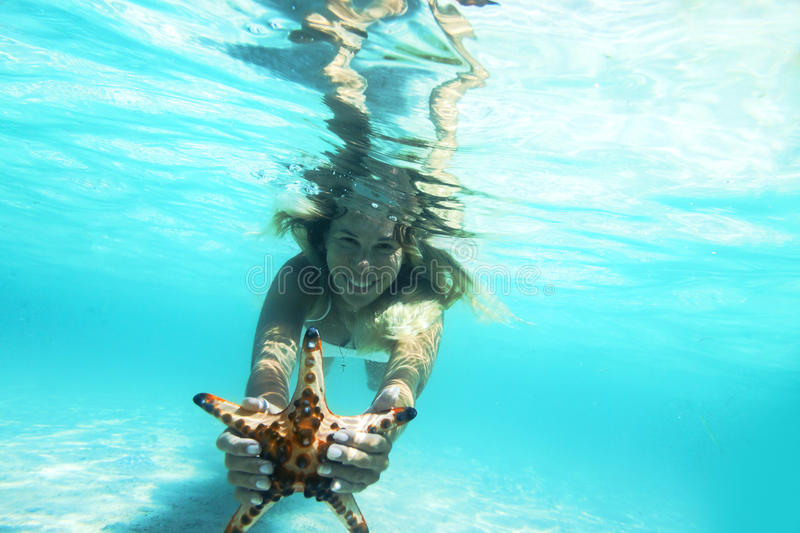 Snorkeling. Woman is snorkeling underwater, showing starfish royalty free stock photography