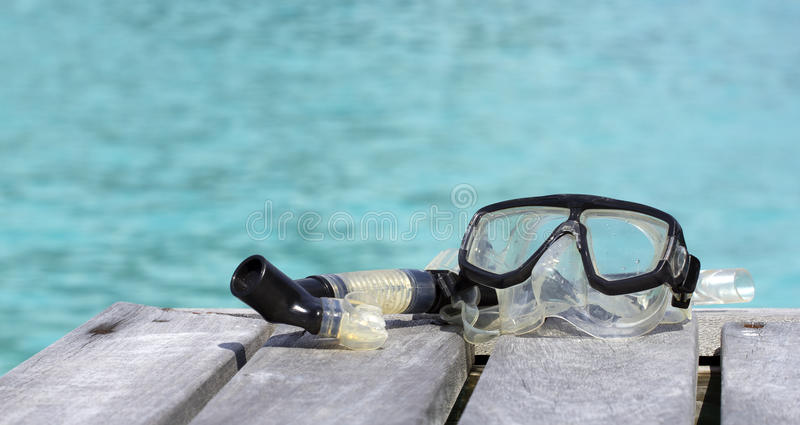 Snorkelling equipment. Closeup of mask and snorkel on a pier by a blue lagoon stock photo