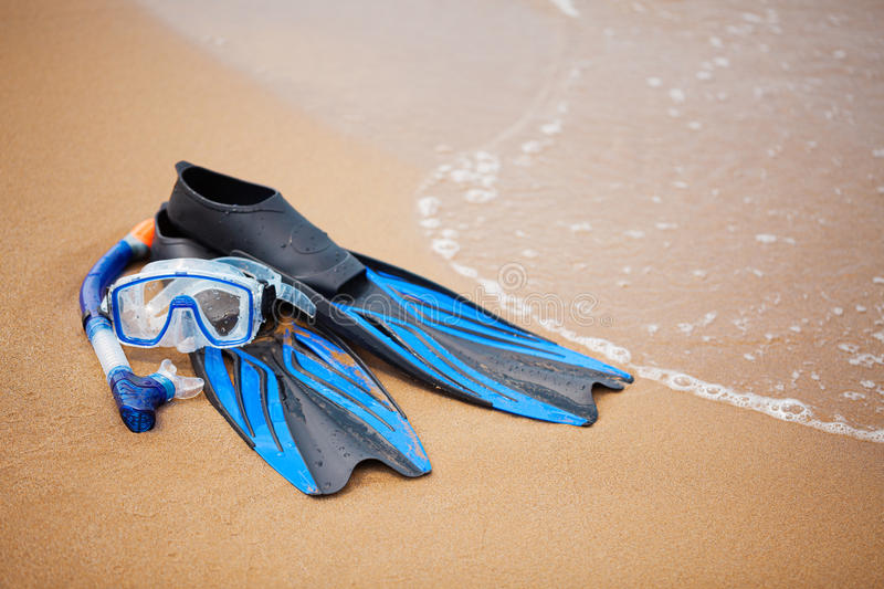 Snorkelling equipment. Swim flippers, mask, snorkel in the surf on the sandy beach; selective focus stock photo