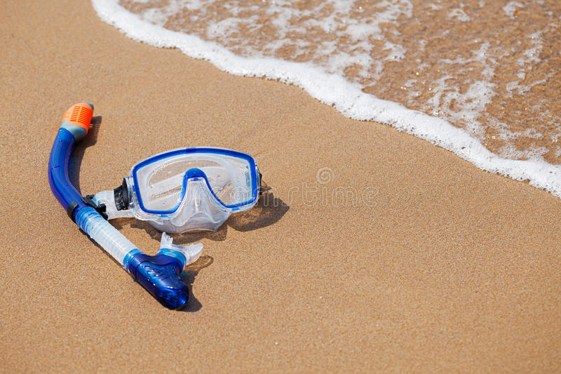 Snorkelling mask. Mask and snorkel in the surf on the sandy beach; selective focus stock images