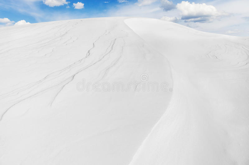 Snow Arctic desert, winter landscape. Snowy arctic desert, winter landscape with snow drifts. Snow dunes on the against white clouds and blue sky background royalty free stock photo