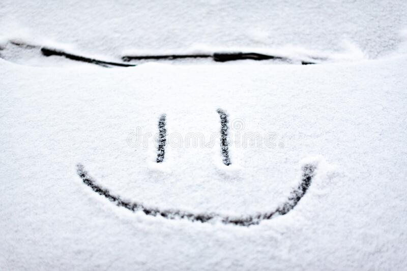 Snow background. Texture of wet snow with a cheerful smiley symbol pattern in the winter window of the car outdoors close-up. royalty free stock image