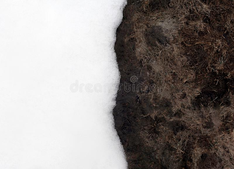 Snow and bare frozen ground background, meeting of winter and spring season royalty free stock photo