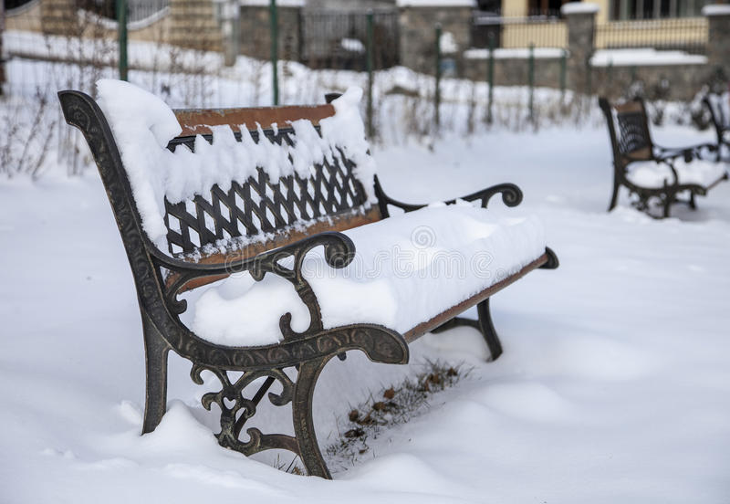 Snow on bench in park of winter. stock image