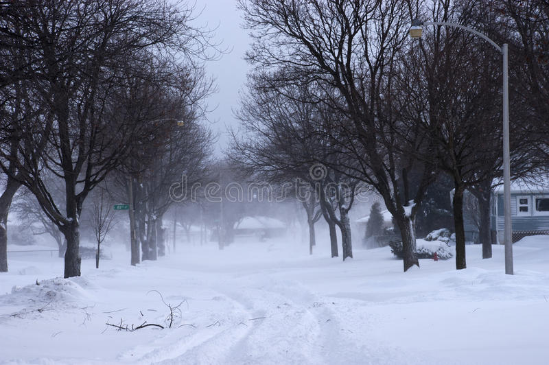 Snow Blizzard on City Street, Neighborhood. A snow blizzard roars through a city street reducing visibility and making it difficult to see houses, homes, and stock photo