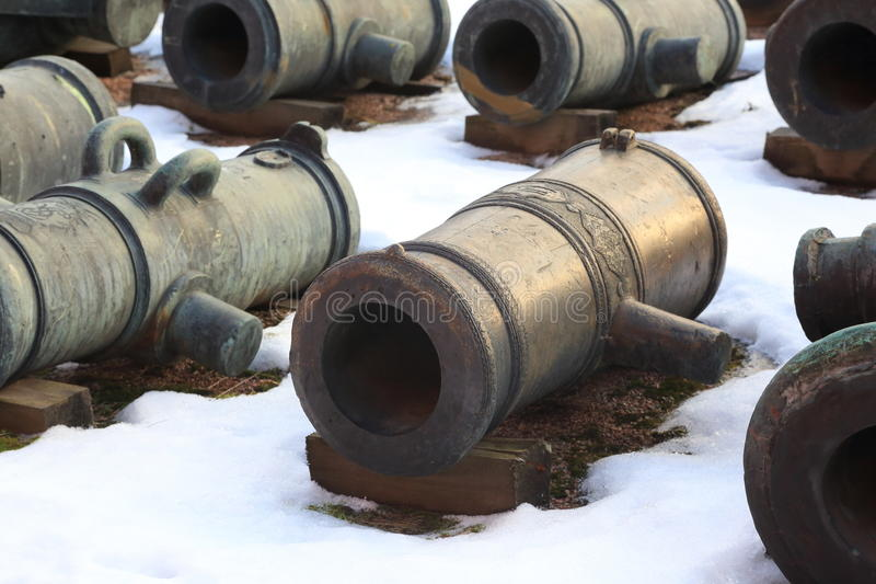 Snow and cannons. The barrels of the old bronze cannons, stacked near the wall of the Museum building. The territory of the Military-historical Museum of stock photos