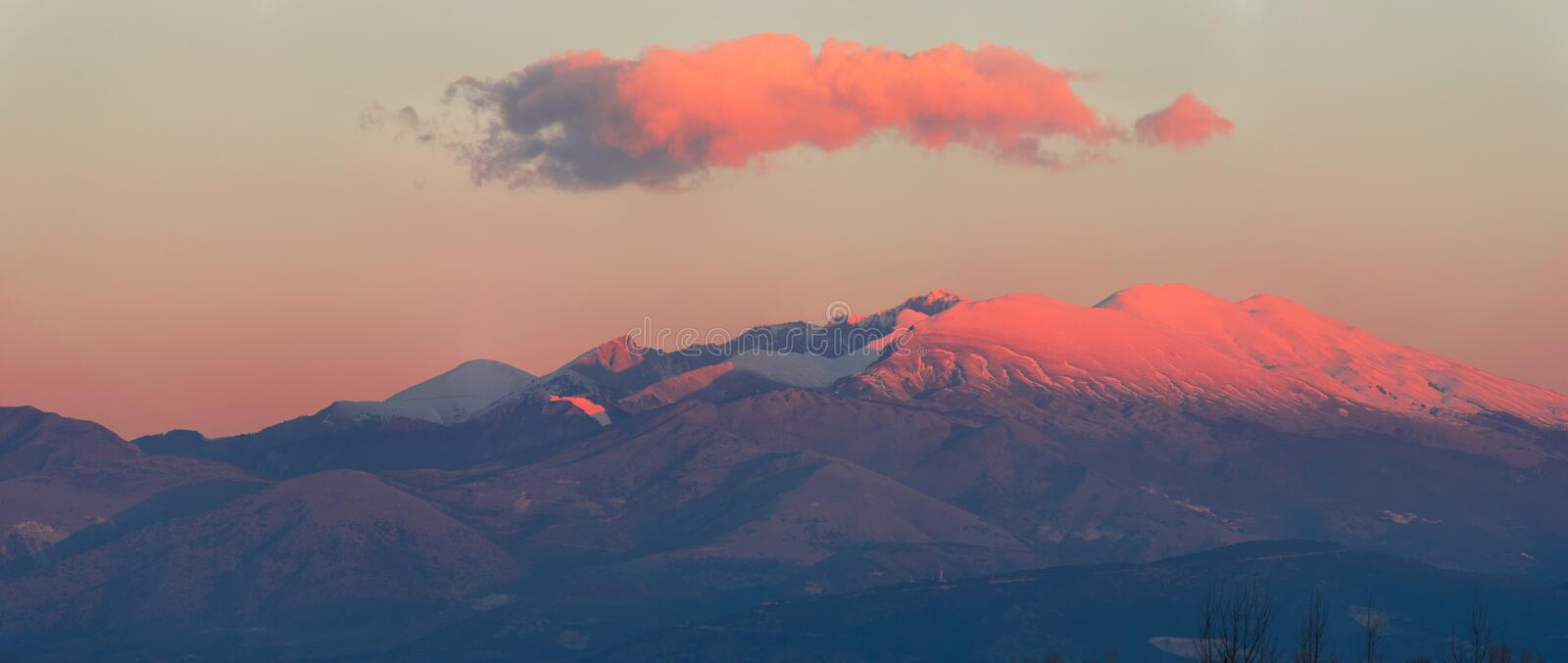 Snow caped mountain peek. A mountain ranges is colored by the first morning light stock photography