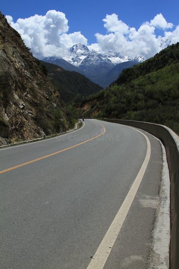 Snow-capped berg och huvudväg royaltyfri fotografi