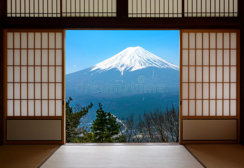 Snow capped Mount Fuji in Japan seen through traditional Japanese sliding paper doors royalty free stock images