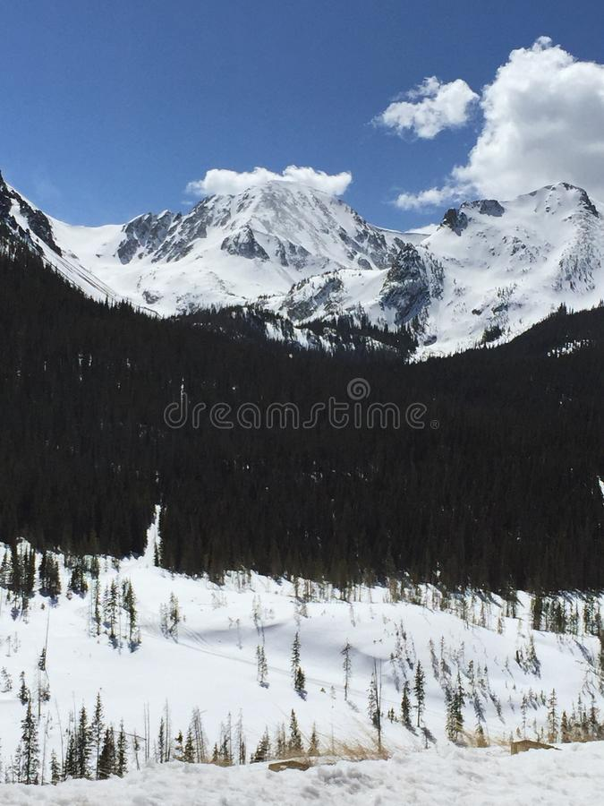 Snow capped mountain peaks against blue sky with puffy white clouds 4. royalty free stock image