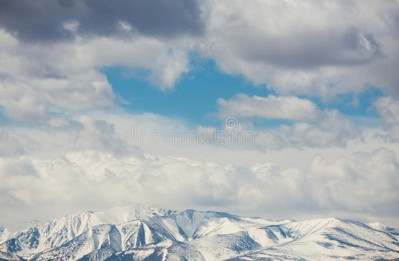Snow-capped mountain peaks. Under the clouds royalty free stock images