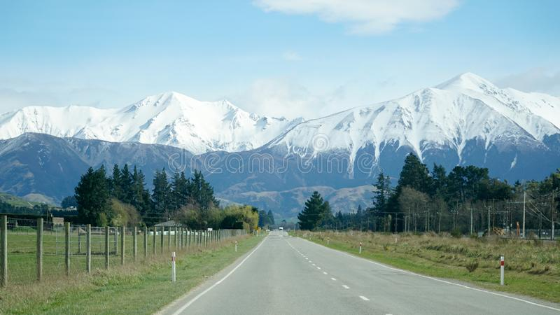 Snow capped Mountains next to the highway in Arthur's Pass National Park, New Zealand. royalty free stock photo