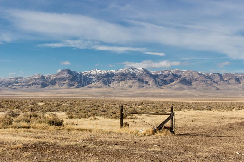 Snow capped mountains in Oregon with blue sky and broken clouds. Snow capped mountains in Oregon with deep blue sky and broken white clouds. Fence and sagebrush stock image