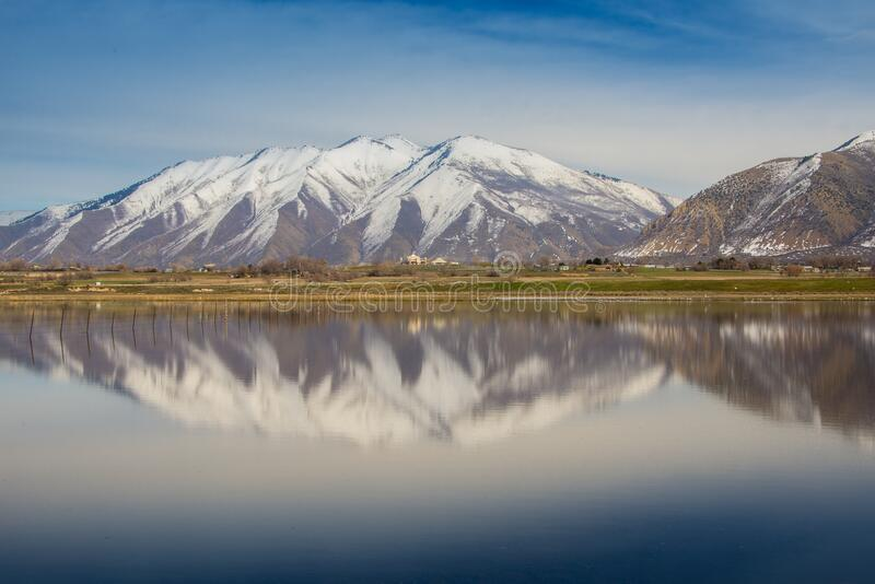 Snow capped mountains reflecting in lake royalty free stock photography