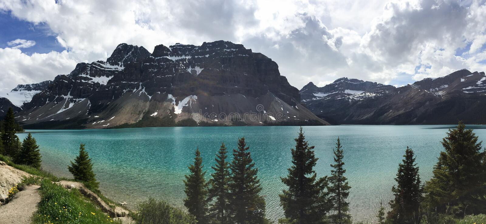Snow-capped mountains rise above a turquoise glacial lake in Banff Canada; panorama stock photos