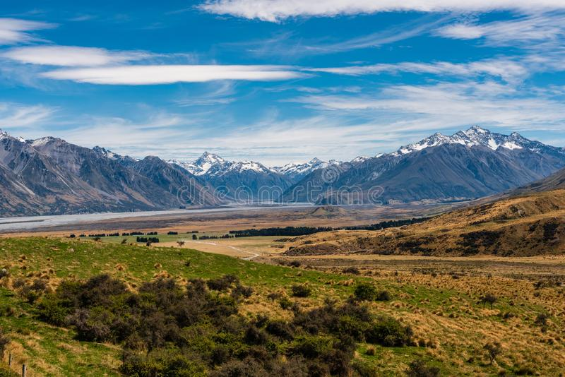 Snow Capped Mountains rise out of the Valley. Photo looking over a valley surrounded by snow-capped mountains in New Zealand stock photo