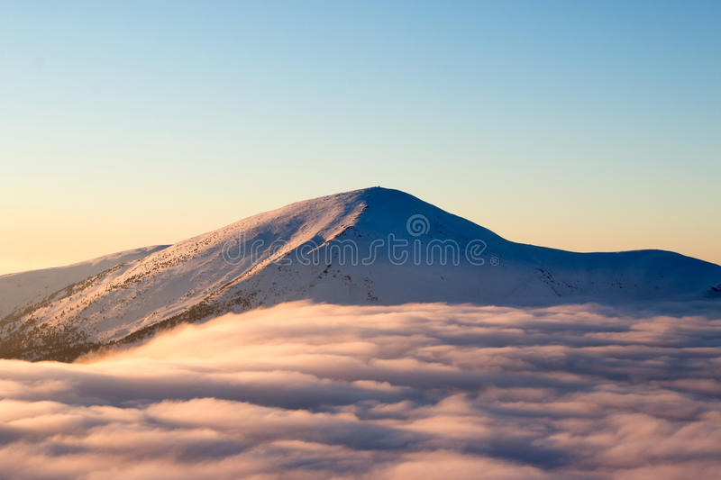 Snow-capped mountains rising above a fluffy cloud, cold, frosty royalty free stock image