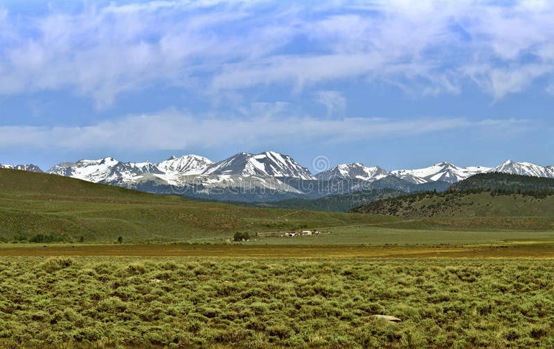 Snow Capped Mountains, Sierra Nevada. A ranch is nestled in the green valley below the rugged snow-capped mountains of the eastern side of the Sierra Nevada stock image