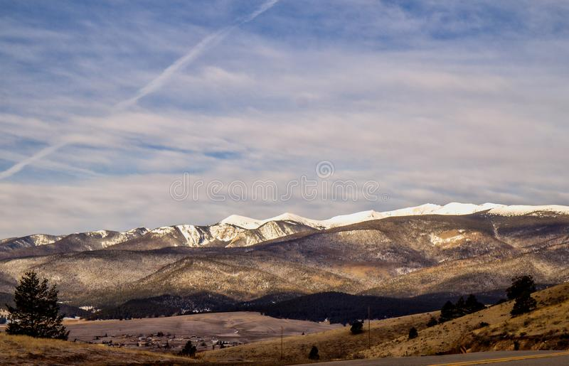 Snow capped mountains in. A small village surrounded by snow capped mountains dotted with green evergreen trees under a cloudy sky in a countrye New Mexico royalty free stock images