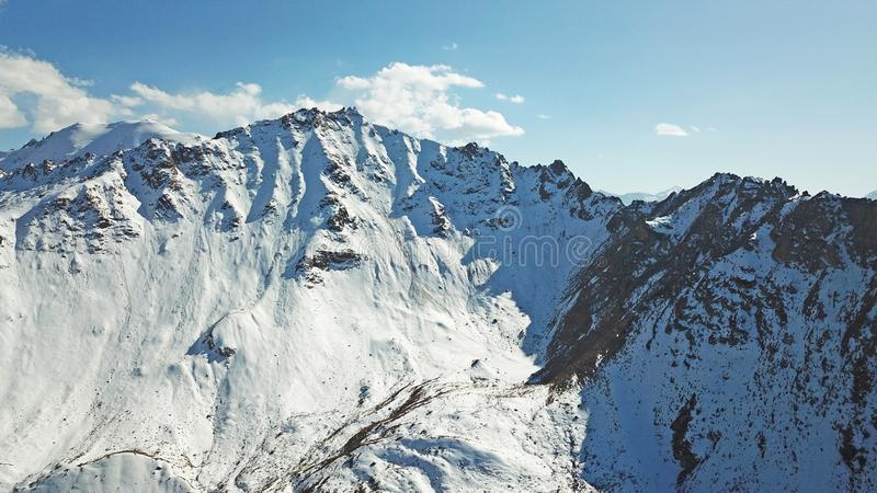 Snow-capped mountains. White clouds and blue sky. Autumn in the mountains, but already lies snow. Height 4000 m. Large stones lie on the slopes. Kazakhstan royalty free stock photography