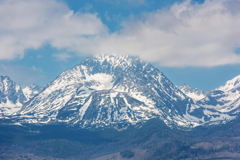 Snow-capped peaks of rocky mountains with blue sky and clouds stock photo