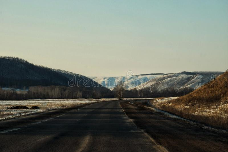Snow-capped peaks of the Ural Mountains. The road along the snowy Ural Mountains stock photography