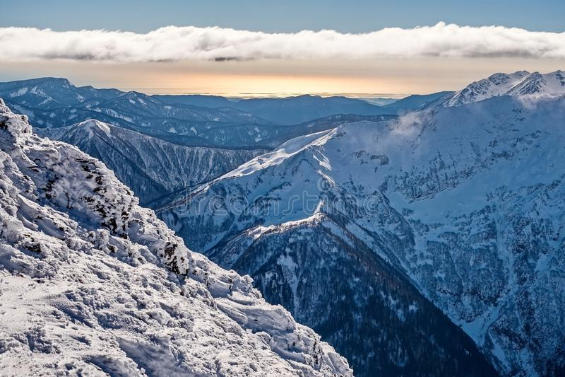 Snow-capped sopki. Alpine landscape. Snow-capped peaks of the Sikhote-Alin Range. Sikhote Alin, a mountainous country royalty free stock images