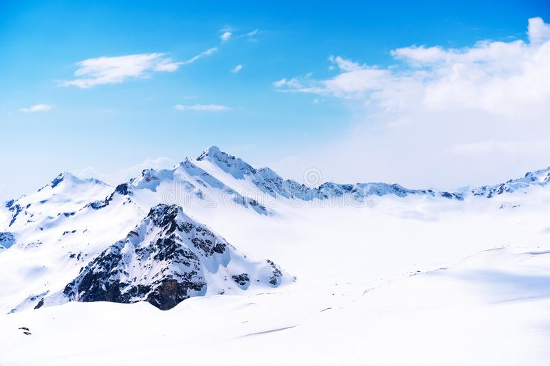 Snow capped summit of Elbrus high under clear blue panoramic skies stock photo