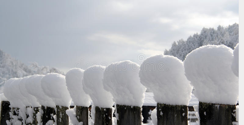 Snow caps. After has passed a wet spring snow on a fence beautiful snow caps were formed royalty free stock photo