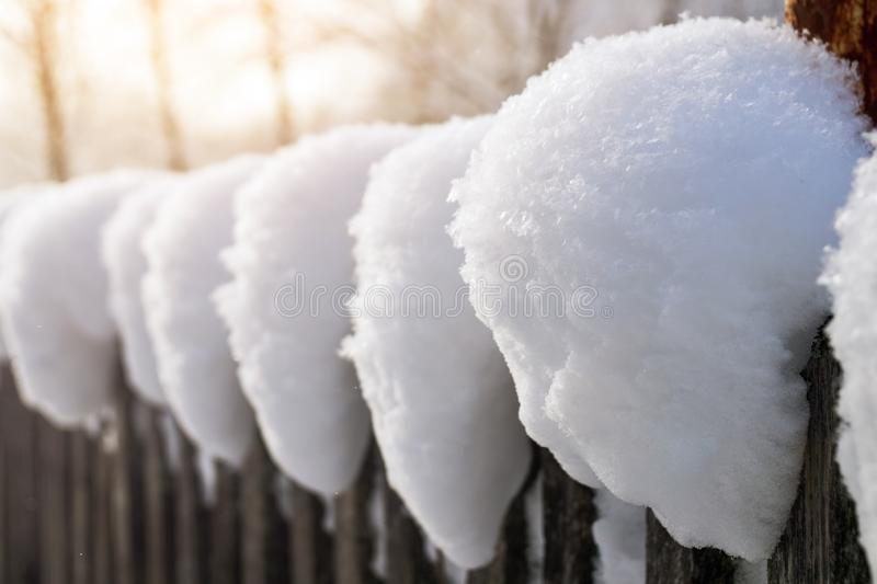 Snow caps on an old wooden country fence back lit by the morning sun. Snow caps on an old wooden country fence back lit by sun rays after a snowfall in winter royalty free stock image