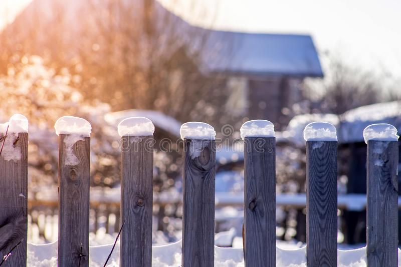 Snow caps on an old wooden country fence backlit by sun rays after a snowfall in winter morning close up. Rural landscape. White, covered, day, thick, tree royalty free stock photo