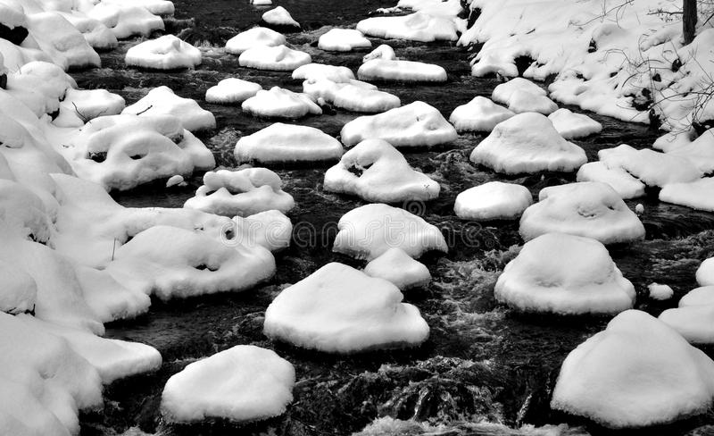 Snow caps on the stones of a mountain stream.  royalty free stock images