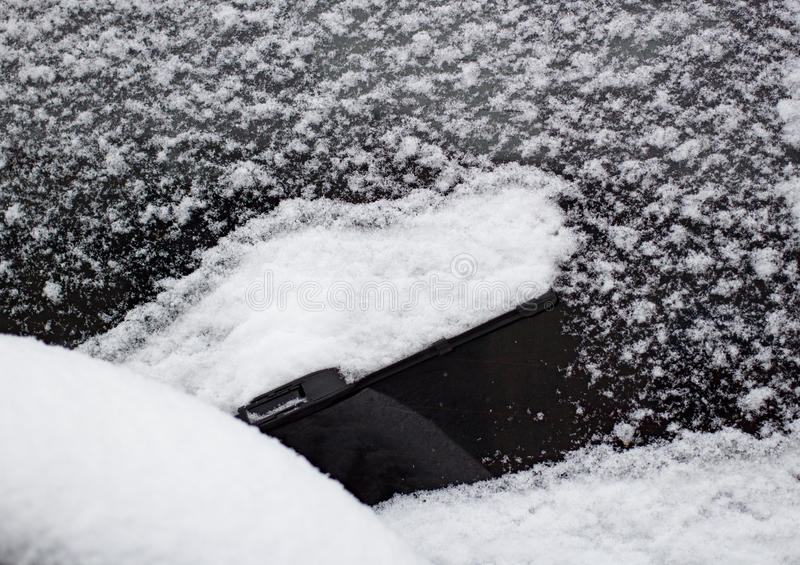 Snow on the car windshield wipers. Day stock photos