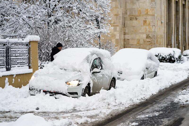 Snow on cars in the morning. Winter season and icy cars on the road in morning rush hour traffic of Bucharest, Romania, 2020 stock photos