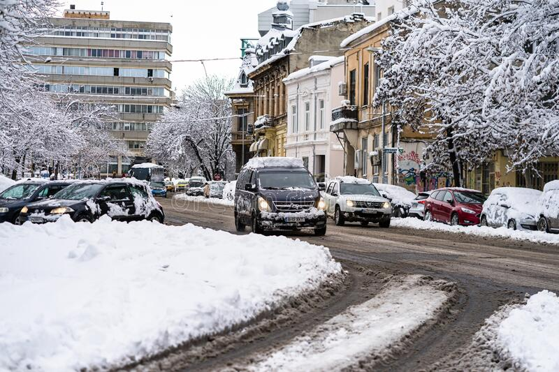 Snow on cars in the morning. Winter season and icy cars on the road in morning rush hour traffic of Bucharest, Romania, 2020 royalty free stock photo