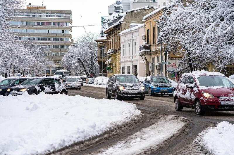Snow on cars in the morning. Winter season and icy cars on the road in morning rush hour traffic of Bucharest, Romania, 2020 stock image