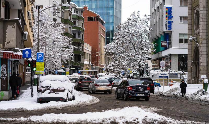 Snow on cars in the morning. Winter season and icy cars on the road in morning rush hour traffic of Bucharest, Romania, 2020 royalty free stock photography