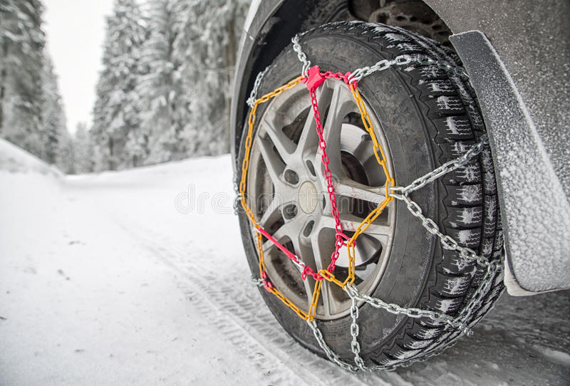 Snow chains on tyre. Snow chains on tire. Detail of wheel in winter forest stock photo