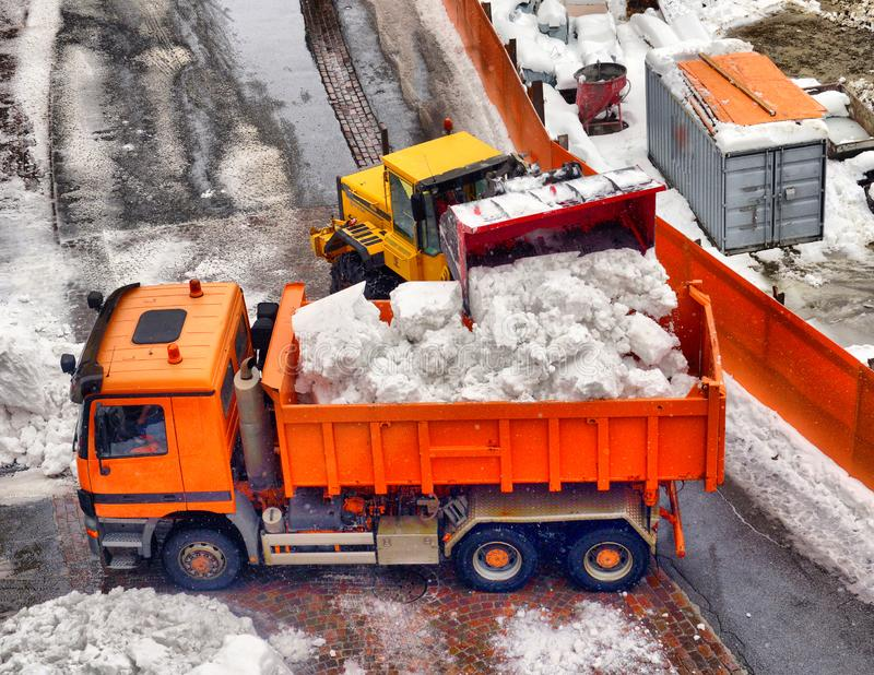 Snow cleaning tractor snow-removal machine loading pile of snow on a dump truck. Snow plow outdoors cleaning street city after. Blizzard or snowfall stock photos