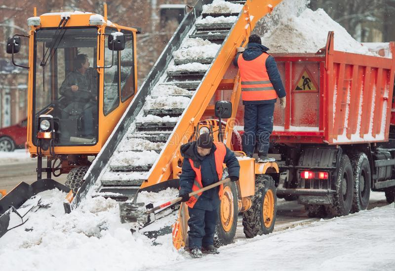 Snow cleaning tractor snow-removal machine loading pile of snow on a dump truck. Snow plow outdoors cleaning street city. After blizzard or snowfall stock images