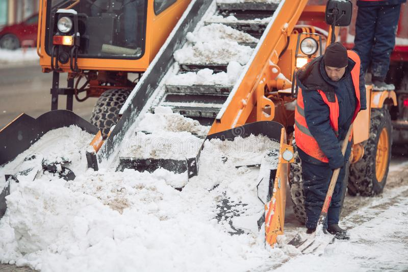 Snow cleaning tractor snow-removal machine loading pile of snow on a dump truck. Snow plow outdoors cleaning street city. After blizzard or snowfall stock photography