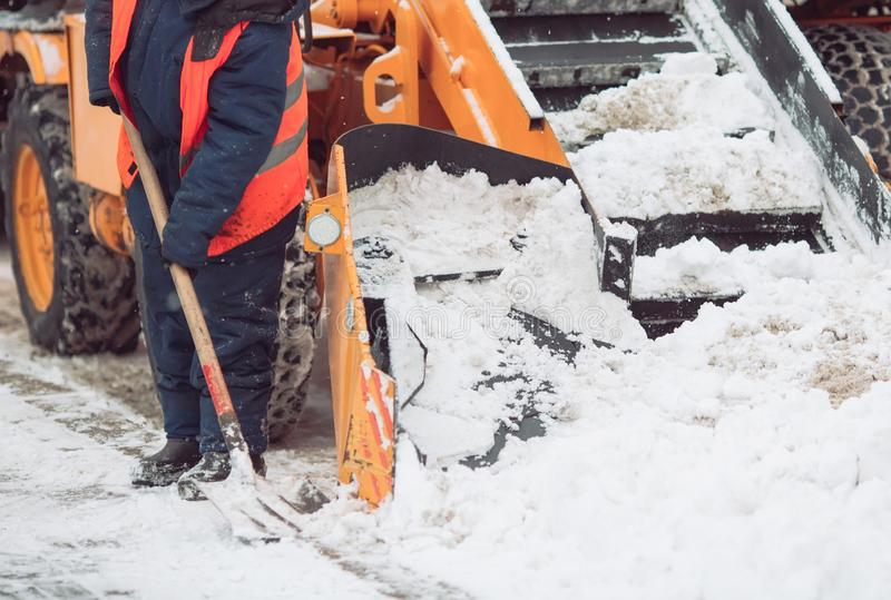 Snow cleaning tractor snow-removal machine loading pile of snow on a dump truck. Snow plow outdoors cleaning street city. After blizzard or snowfall royalty free stock images