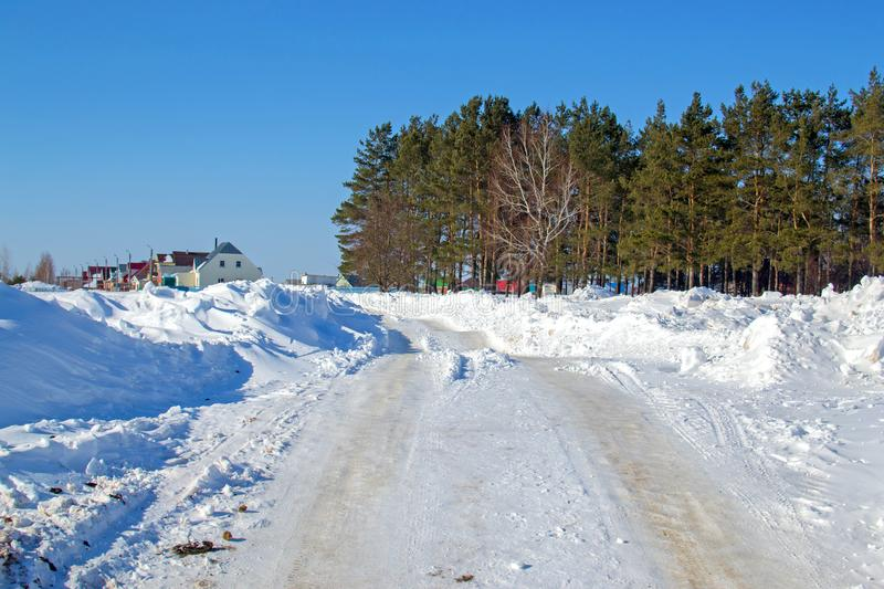 Snow-cleared road to the village. The tractor cleared the road stock photography