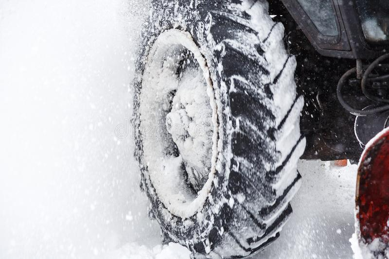Snow clearing. Tractor clears the way after heavy snowfall. close up of tires. Snowblower grader clears snow covered road royalty free stock photos