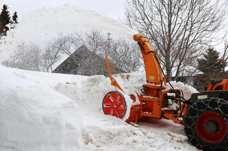 Snow clearing work with a large snow blower in winter stock photography