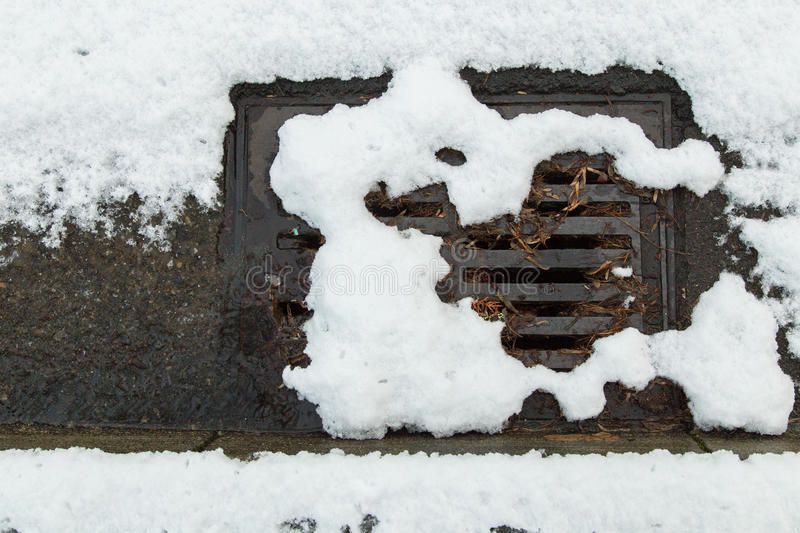 Snow clogged street drain. Snow clogging a street drain royalty free stock images