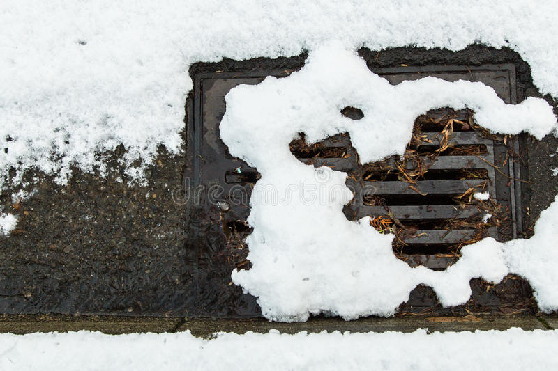 Snow clogged street drain. Snow clogging a street drain royalty free stock photos