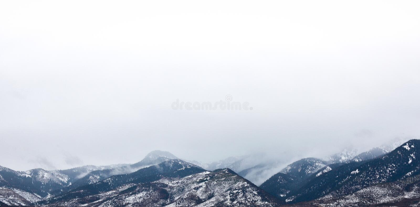 Snow Coated Mountain Under White Clouds stock photos