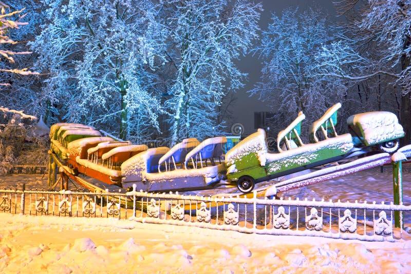 Snow-covered aantrekkelijkheden in het oude park stock foto